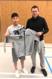 Ziyao bekommt von Roland Rottwilm eine Trainingsjacke überreicht.